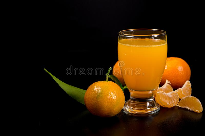 Mandarin juice on black background. Mandarin juice with mandarins and slices on black background royalty free stock photos