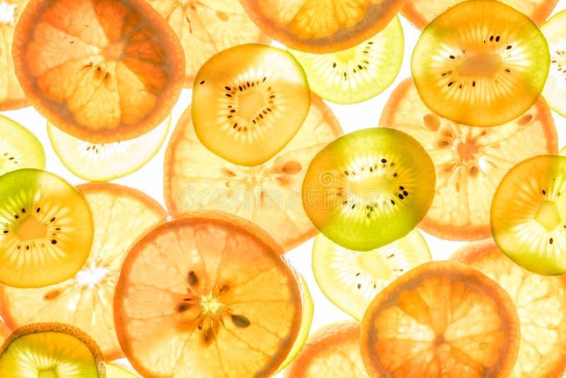 Mandarin and kiwi slices on white. Mandarin and kiwi slices in different colors on white background stock images