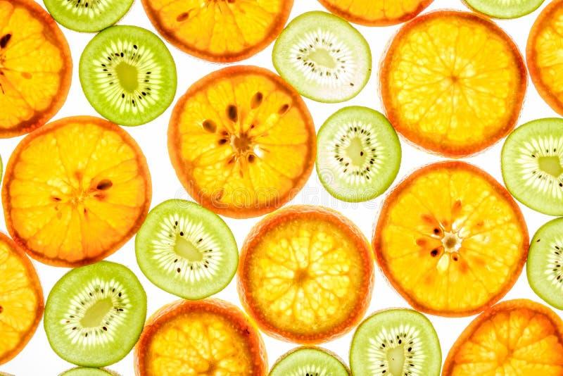 Mandarin and kiwi slices on white. Mandarin and kiwi slices in different colors on white background stock photo