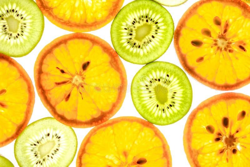 Mandarin and kiwi slices on white. Mandarin and kiwi slices in different colors on white background stock photos