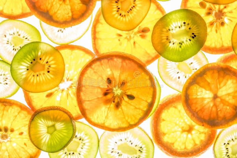 Mandarin and kiwi slices on white. Mandarin and kiwi slices in different colors on white background stock photography