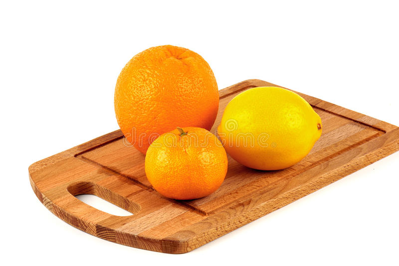 Mandarin, lemon and orange on a wooden cutting board. On a white background stock photos