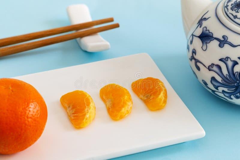 Mandarin, mandarijn, of clementine met gepelde segmenten of plakken op rechthoekplaat met Chinese theepot en eetstokjes stock afbeeldingen
