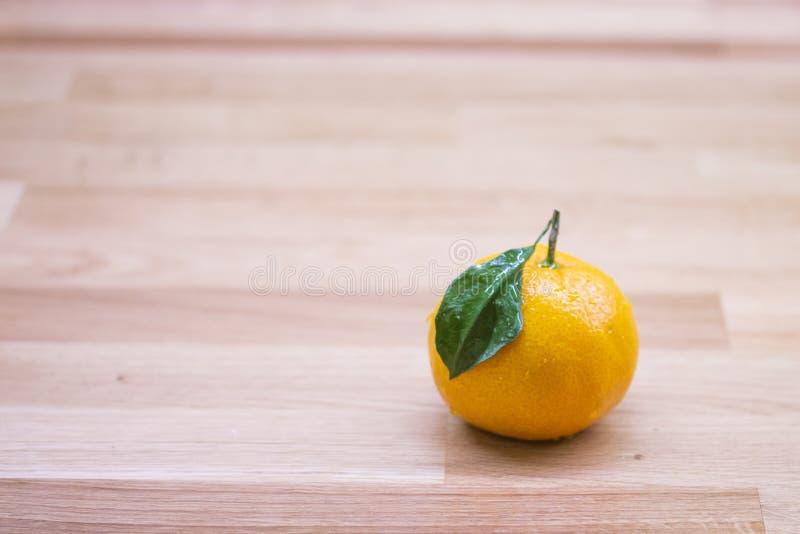 Mandarin met een blad en een handvat op een houten lijst Smakelijke rijpe gehele oranje citrusvruchtenmandarijn met groen blad Sa stock afbeeldingen