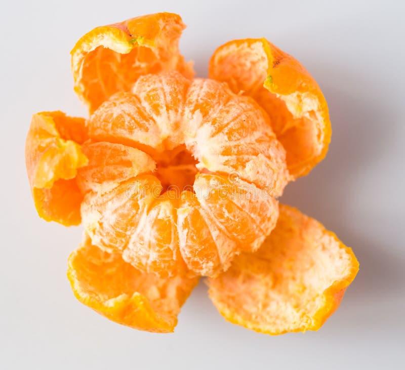Mandarin with peeled peel on white background royalty free stock photo