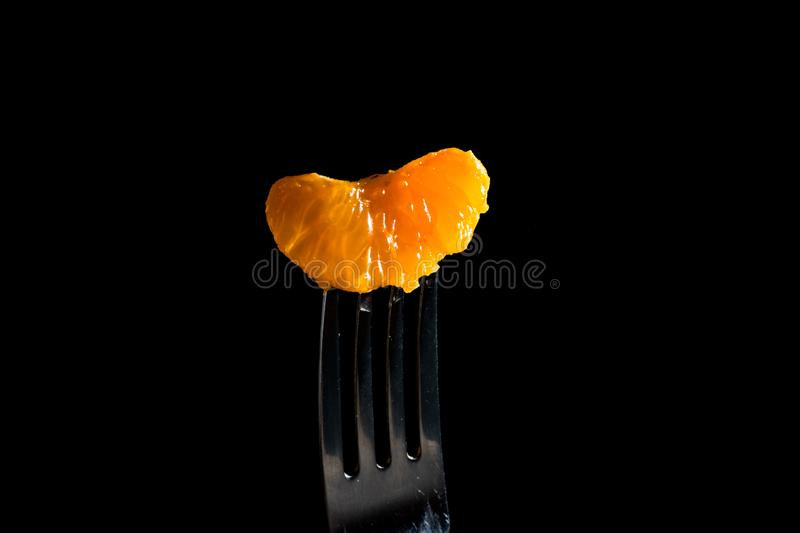 Mandarin pierced on a fork isolated on a black background stock photo