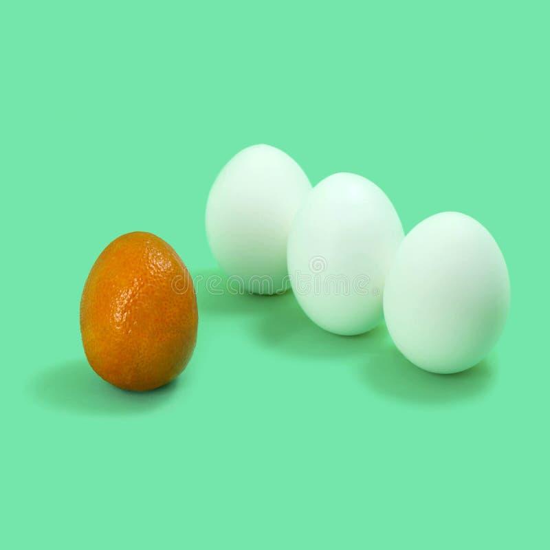 Mandarin of unusual shape and three eggs stock photography