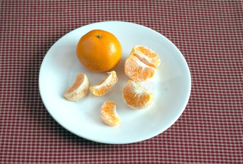 Mandarina con las rebanadas en una placa que miente en mantel a cuadros Primer de la foto imágenes de archivo libres de regalías