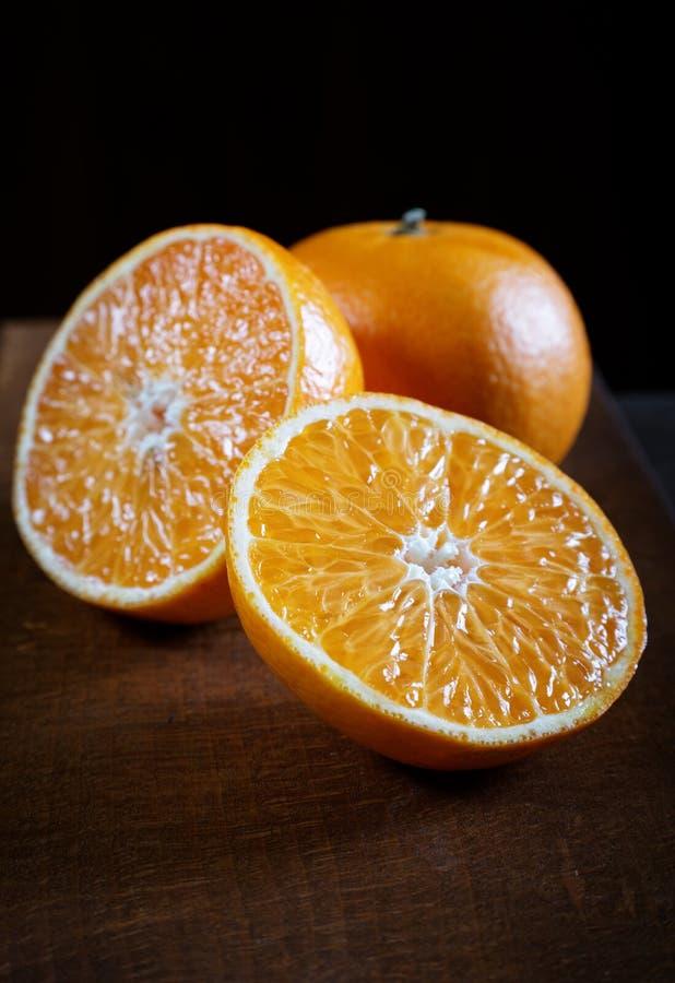 Mandarina cortada en una tabla vieja fotografía de archivo