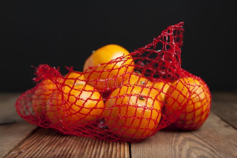 Mandarina de los agrios en naranjas en paquete plástico del bolso neto Ningún concepto plástico Empaquetando que no recicla plást fotos de archivo libres de regalías