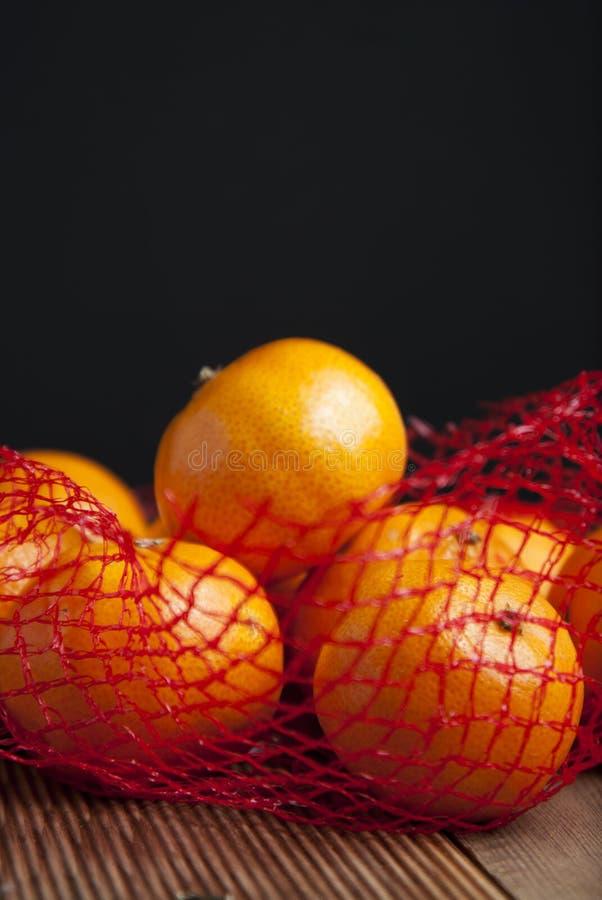 Mandarina de los agrios en naranjas en paquete plástico del bolso neto Ningún concepto plástico Empaquetando que no recicla plást imagen de archivo