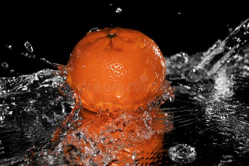 Mandarina que cae en el agua en el espejo negro foto de archivo