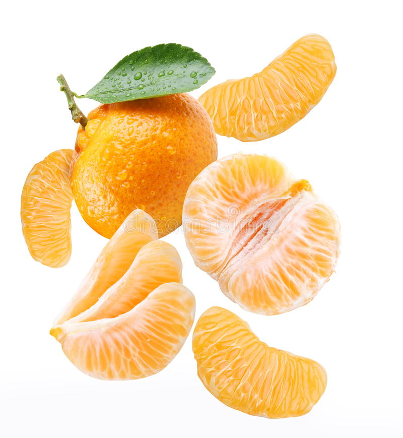 Mandarina y rebanadas de la mandarina que caen. imagen de archivo