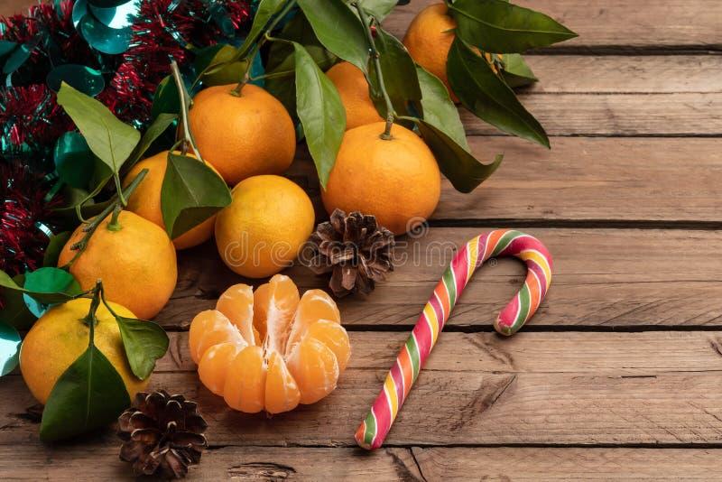 Mandarinas anaranjadas con las hojas en un fondo de madera, Año Nuevo fotografía de archivo libre de regalías