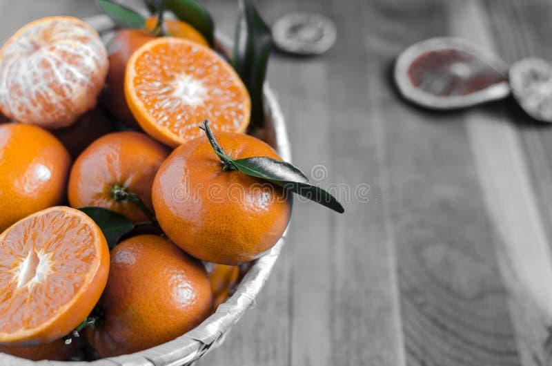 Mandarinas con las hojas en una cesta en un primer blanco y negro del fondo, espacio de la copia foto de archivo libre de regalías