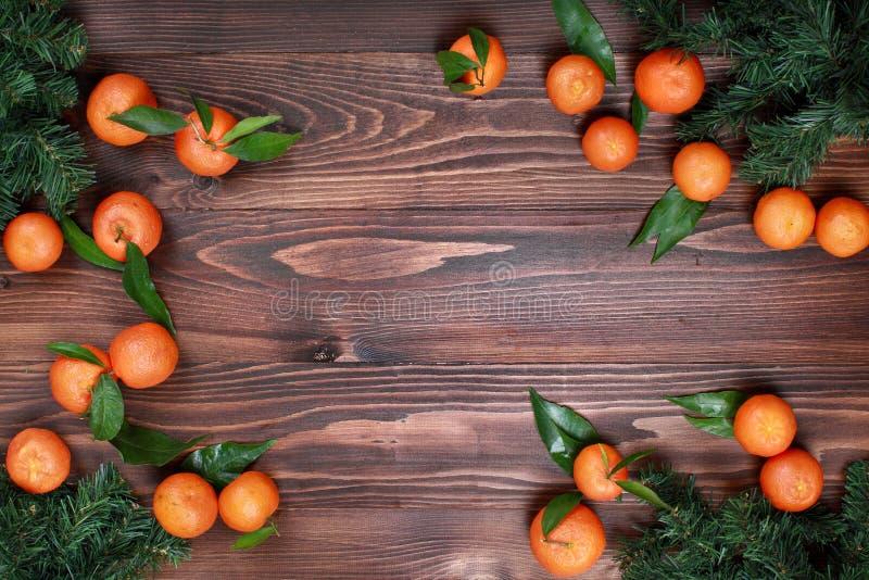 Mandarinas con las hojas y el árbol de navidad en la visión superior superficial de madera imágenes de archivo libres de regalías