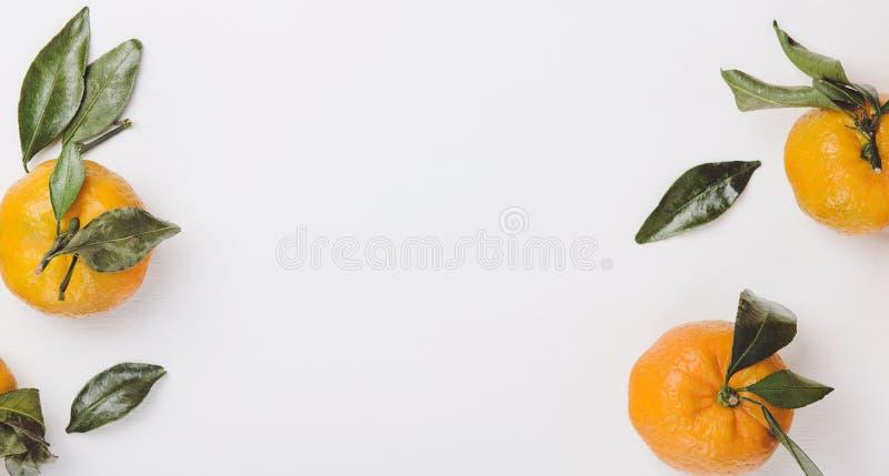 Mandarinas dulces anaranjadas con las hojas verdes en un fondo blanco bajo la forma de marco Copie el espacio, visión superior, e fotos de archivo