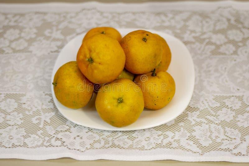 Mandarinas en la placa y las toallas blancas foto de archivo
