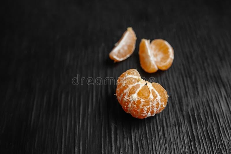 Mandarinas en un fondo negro Porciones de fruta fresca - mandarines imagenes de archivo