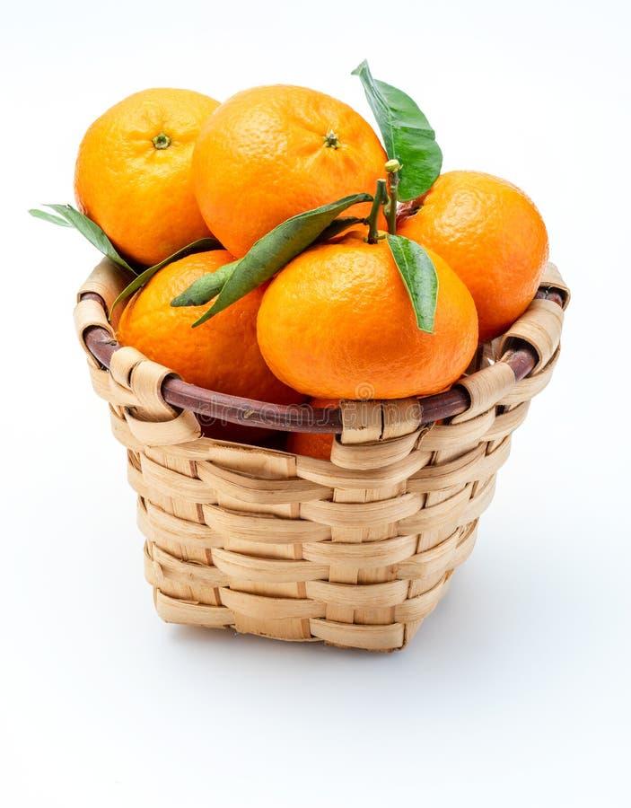 Mandarinas frescas y crudas con las hojas verdes en cesta de mimbre r?stica. Aislado en el fondo blanco fotografía de archivo