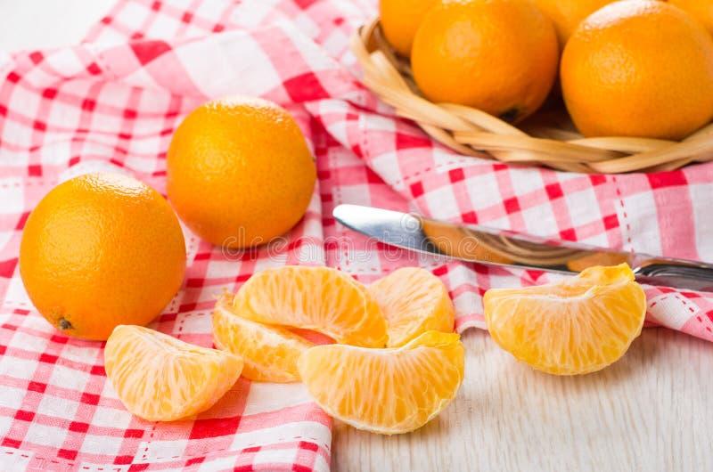 Mandarinas maduras en cesta de mimbre, rebanadas de mandarina y cuchillo imagenes de archivo