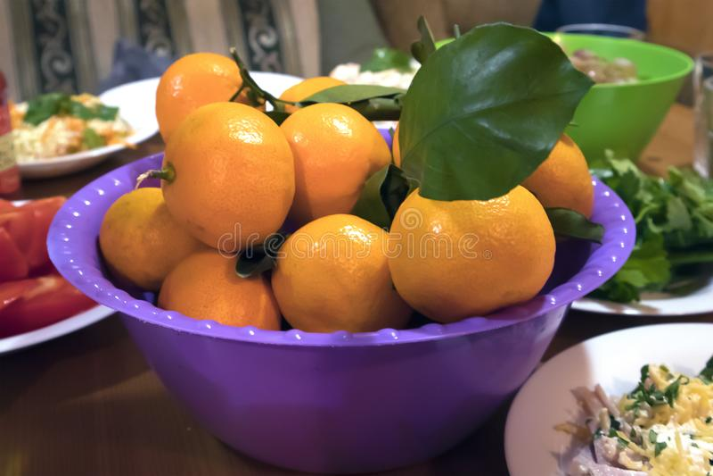Mandarinas maduras jugosas con la hoja verde fresca en un cuenco plástico violeta imagenes de archivo