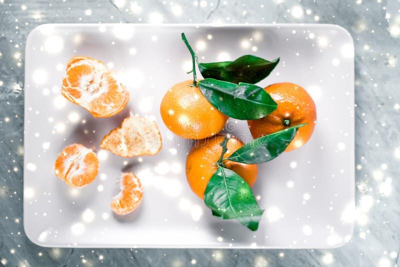 Mandarinas, mandarines, clementinas en tiempo de las vacaciones de invierno, agrios en la placa con nieve que brilla intensamente fotografía de archivo