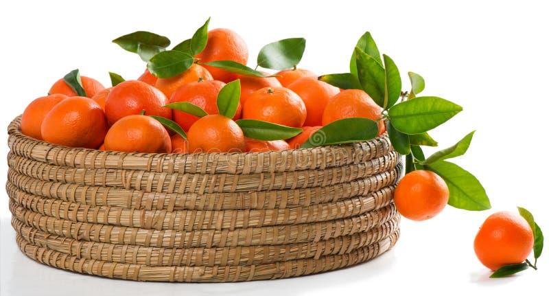 Mandarinas o mandarines con las hojas en una gran cesta imagenes de archivo