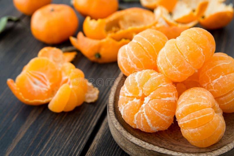 Mandarinas peladas de la clementina en una placa de madera del arte foto de archivo libre de regalías