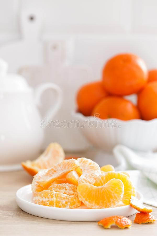 mandarinas Mandarinas peladas sabrosas dulces en la placa en el primer blanco del fondo de la cocina imagenes de archivo