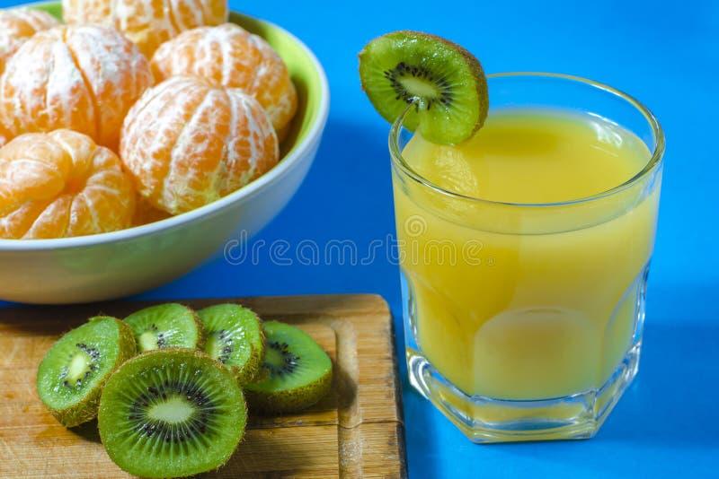 Mandarinas y kiwi El jugo se vierte en un vidrio fondo azul, primer foto de archivo