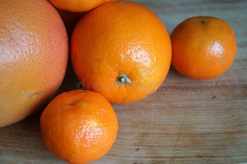 Mandarinas y naranjas con la cáscara de naranja fotografía de archivo