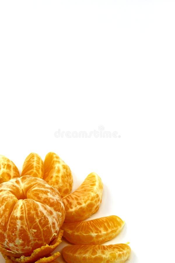 Mandarine épluchée entière fraîche en cercle des tranches d'une autre mandarine sur un fond blanc image libre de droits