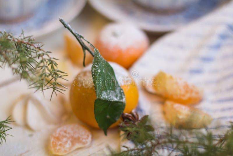 Mandarine couverte du sucre en poudre De Noël toujours durée Mandarine et tasses de thé sur un fond en bois blanc photos stock