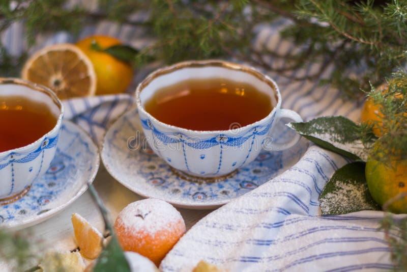 Mandarine couverte du sucre en poudre De Noël toujours durée Mandarine et tasses de thé sur un fond en bois blanc photographie stock libre de droits