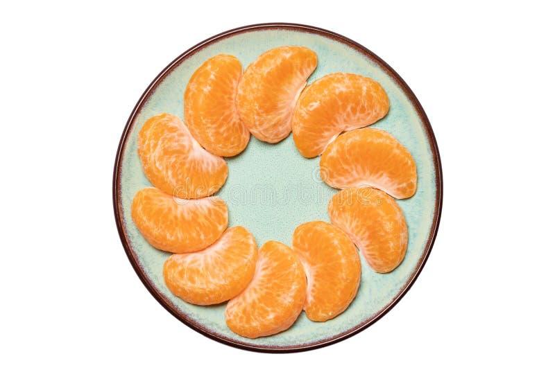 Mandarine isolated. Close-up of fresh ripe peeled mandarin orange tangerine or clementine on a plate isolated on a white royalty free stock photos