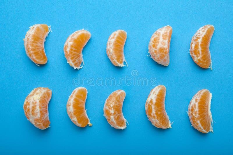Mandarine plak op blauwe achtergrond Reeks van rijpe mandarine plak royalty-vrije stock foto's