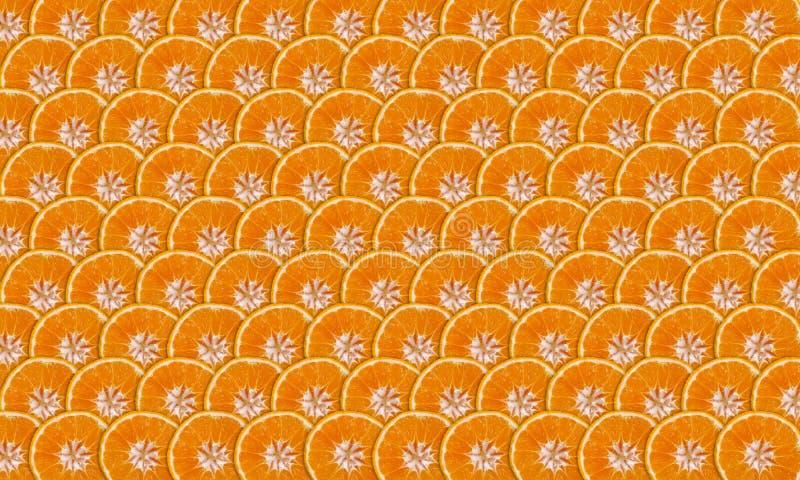 Mandarine slices. Thin mandarines slices folded into rows as background royalty free stock photo