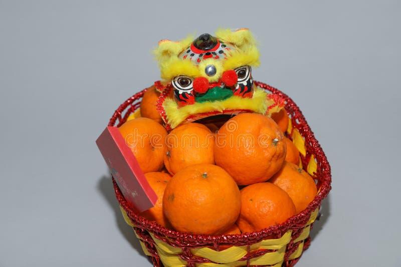 Mandarinen des Chinesischen Neujahrsfests im Korb verzieren mit chinesischem Drachen, Frühlingsfest, ANG-pao stockbild