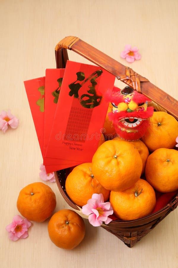 Mandarinen im Korb mit chinesischen roten Paketen des neuen Jahres und Minilöwepuppe lizenzfreie stockfotografie