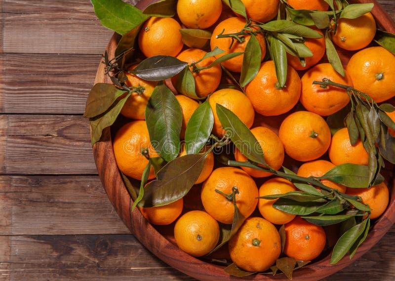Mandariner med sidor i träplatta på lantlig wood bakgrund royaltyfria foton