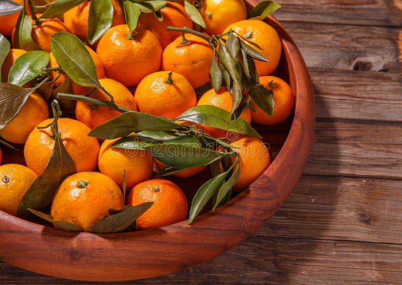 Mandariner med sidor i träplatta på lantlig wood bakgrund royaltyfria bilder