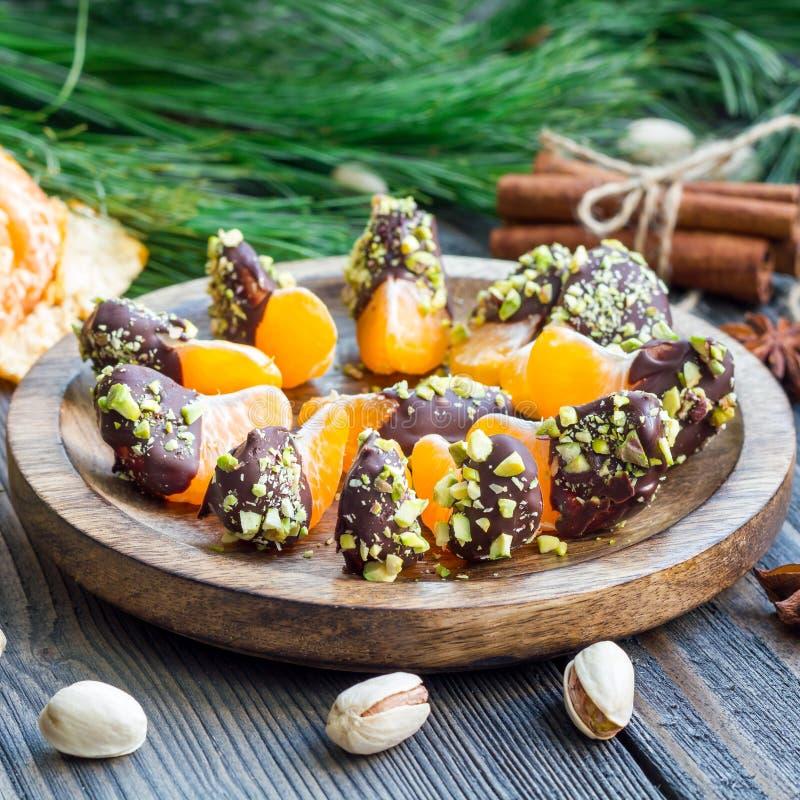 Mandariner som täckas med choklad och pistaschen, fyrkant royaltyfria foton