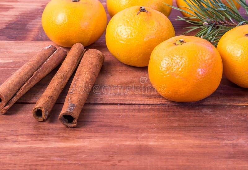 Mandarines dans un panier avec les branches de sapin, bâtons de cannelle sur un fond en bois photographie stock