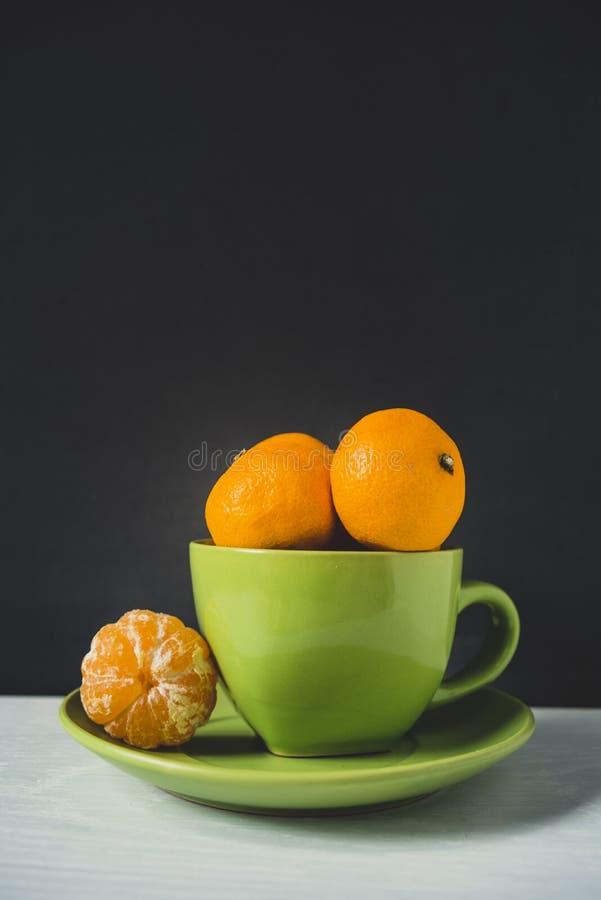 Mandarines dans une tasse verte photos libres de droits