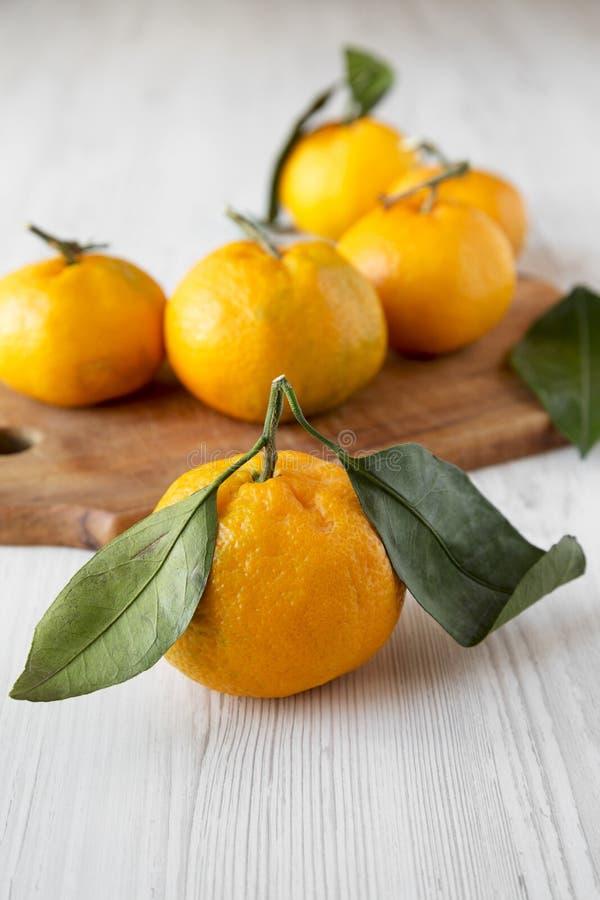 Mandarines juteuses mûres fraîches au-dessus de la surface en bois blanche, vue de côté Foyer sélectif photo stock
