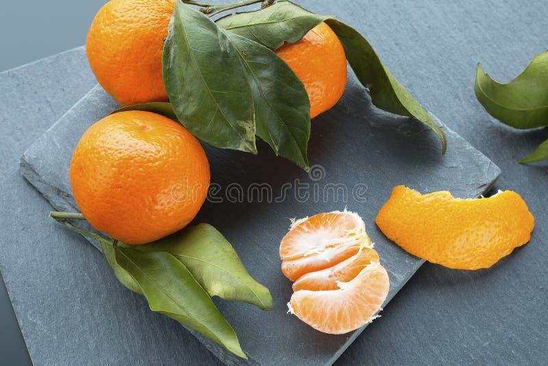 Mandarines lumineuses avec des feuilles sur le fond de plat d'ardoise image libre de droits