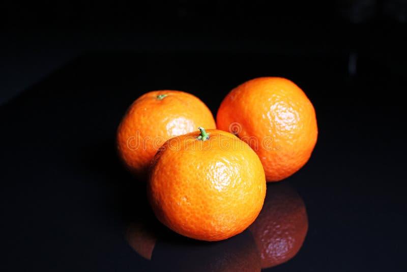 mandarines Mandarines oranges de fruit d'agrume de mandarine sur le fond réfléchi noir de studio miroir brillant noir reflété de  photo stock