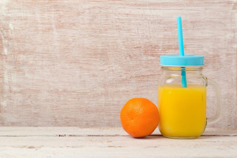 Mandarinesaft im Weckglas und in der Frucht über hölzernem Hintergrund mit Kopienraum Gesunde Ernährung oder Nähren lizenzfreie stockfotos