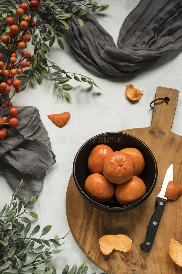 Mandarini in ciotola nera, tagliere di legno fotografie stock